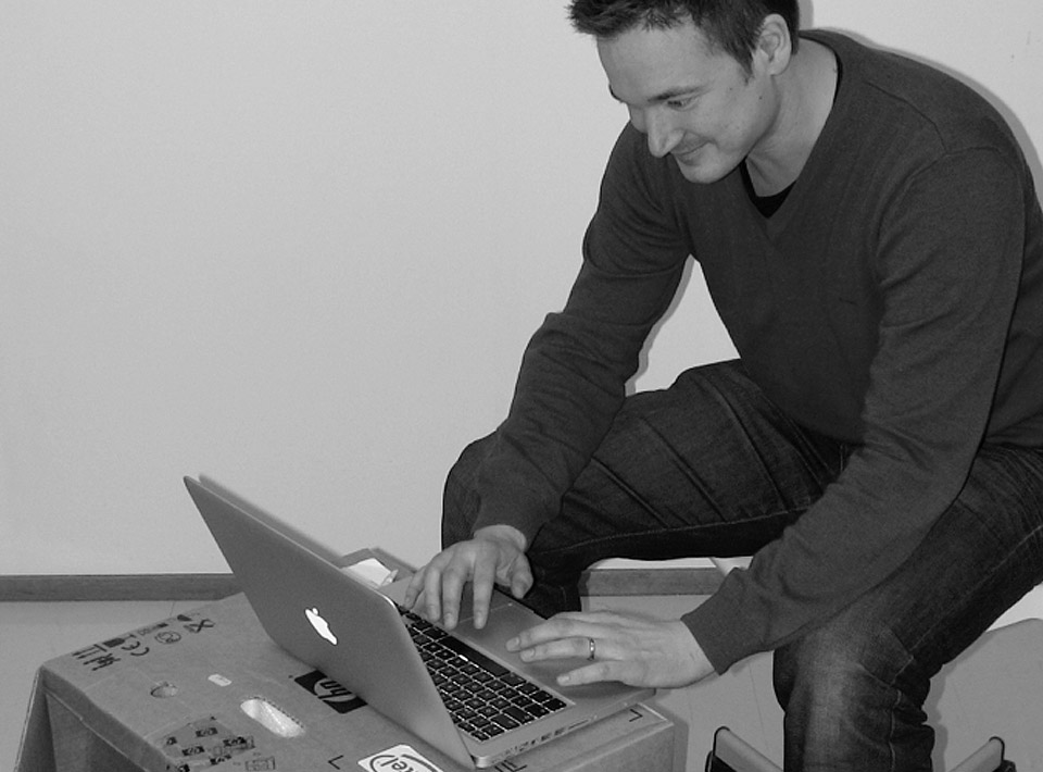 Ilkka sitting at his cardboard desk at the Espoo office.